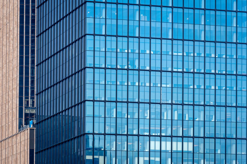 Close-up of glass office building facade with windows, texture, architecture