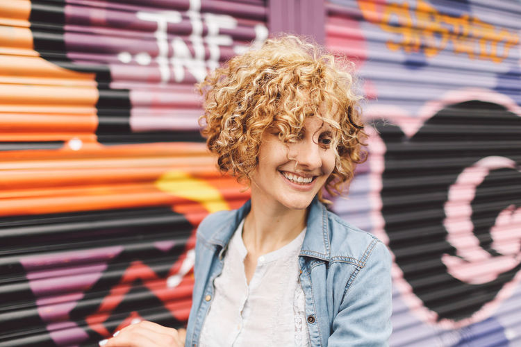 Blonde Brighton Casual Clothing Close-up Curly Hair Day Focus On Foreground Front View Girl Graffiti Graffiti Art Headshot Joyful Jumping Lifestyles Playful Portrait Selective Focus Smiling Spinning Street Streetart People And Places Moments Of Happiness