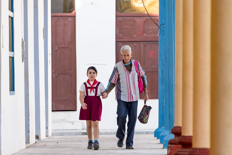 Cuban pioneer and her father going to school early in the morning. Education is one of the greatest achievement of the Cuban revolution Adult Boys Cheerful Child Childhood City Confidence  Day Females Friendship Full Length Girls Happiness Lifestyles Outdoors People Smiling Togetherness Two People
