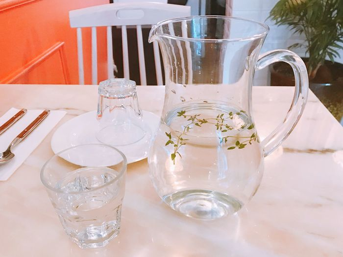 Water with herb in jug on table