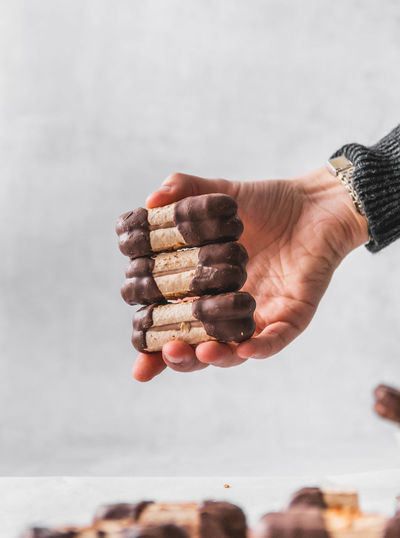 Close-up of hand holding stack against white background