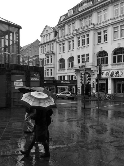 Full length of man with umbrella in city against sky