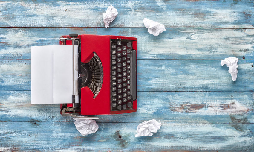 High Angle View Of Typewriter Amidst Papers On Table