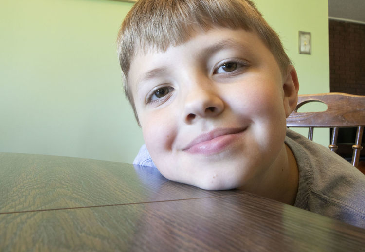 An nine-year-old boy rests his head on a dining room table while smiling. Portrait Headshot Front View One Person Child Indoors  Childhood Boys Real People Smiling Looking At Camera Males  Table Lifestyles Leisure Activity Men Close-up Innocence Contemplation Human Face Wide Angle Wide Angle Distortion Home Happiness Love Boy Boyhood Dinning Room Dining Room Table Chair Hanging Out