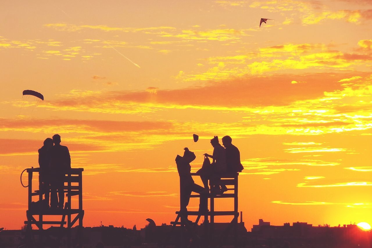 Silhouette People Against Orange Sunset Sky