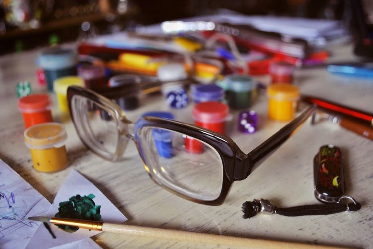 Close-up of eyeglasses with paints on table