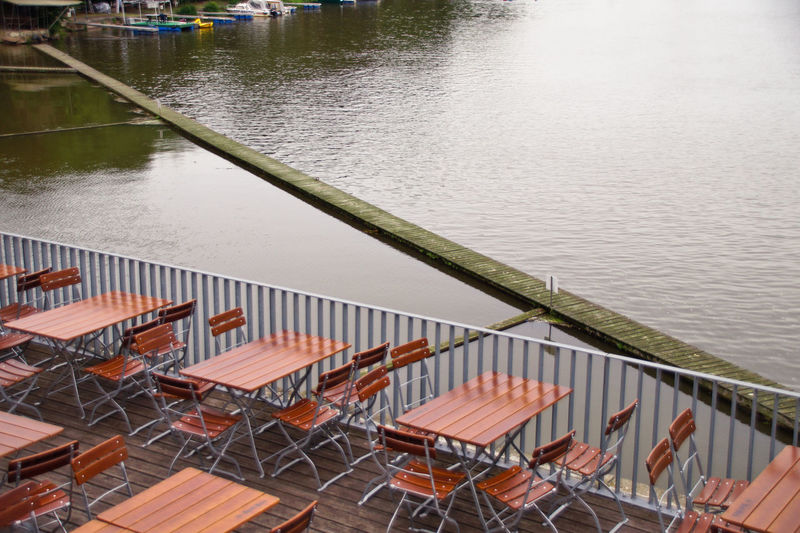 High angle view of tables and chairs by lake