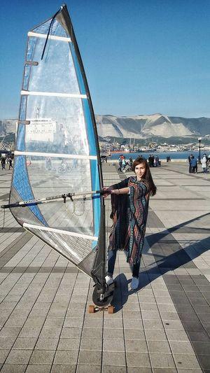 Portrait Of Woman Windsurfing On Street Against Sky