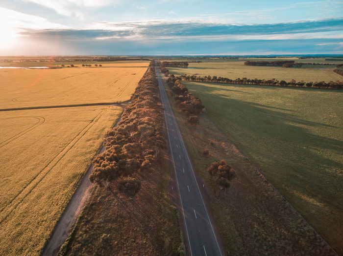 Aerial view of rural road passing through agricultural land in Australian countryside at sunset Beauty In Nature Cloud - Sky Day Landscape Nature No People Outdoors Road Scenics Sky