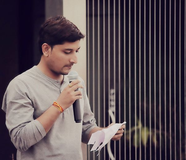 Young man announcing while holding microphone