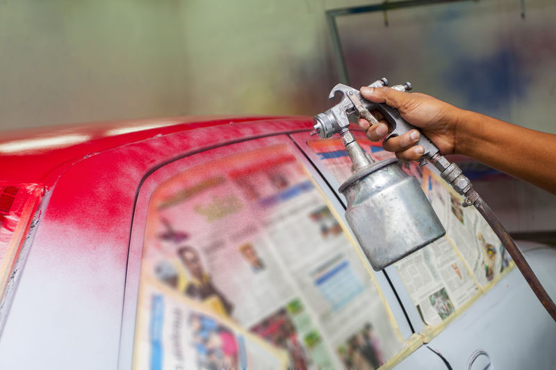 Cropped worker hand painting red on car at garage