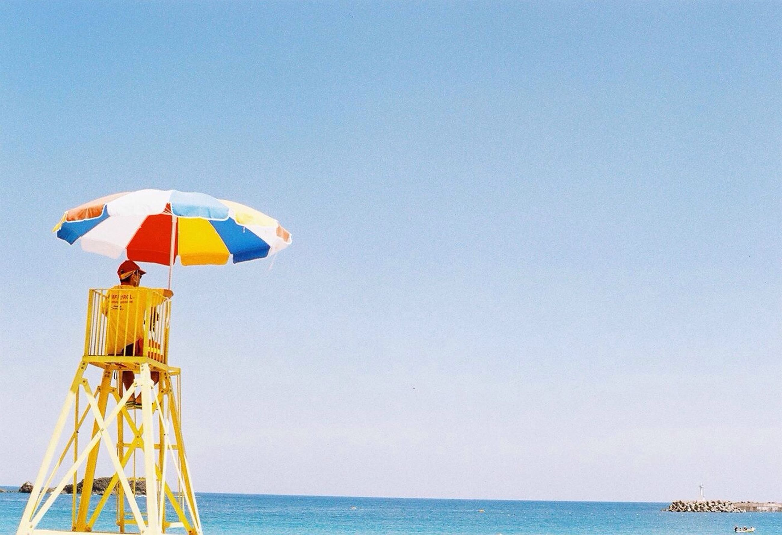 sea, clear sky, horizon over water, water, copy space, blue, beach, tranquility, tranquil scene, scenics, flag, nautical vessel, nature, transportation, beach umbrella, beauty in nature, sky, protection, vacations, day