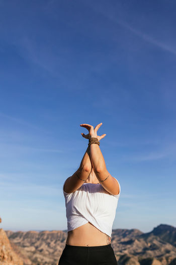 Woman with arms raised standing on land against sky