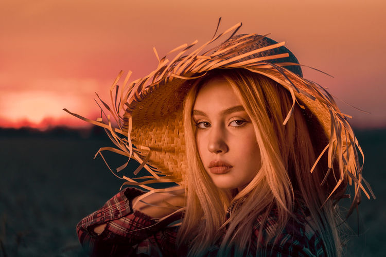 Portrait of woman wearing hat outdoors during sunset