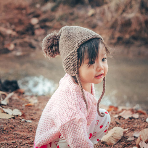 Cute baby girl looking away while crouching on land during winter
