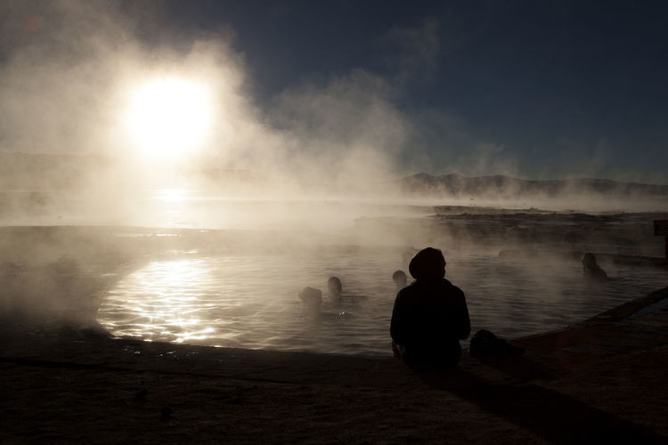 Aguas Termales de Polques Aguas Termales Amanecer Beach Beauty In Nature Group Of People Hot Spring Land Leisure Activity Lifestyles Men Nature Outdoors People Real People Rear View Salar De Uyuni Scenics - Nature Sea Silhouette Sitting Sky Sol Steam Tranquil Scene Water