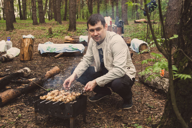 Man Preparing Food On Barbecue Grill In Forest