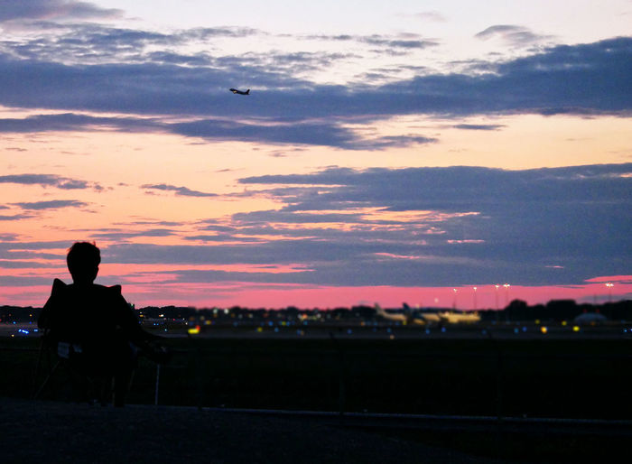 Rear view of silhouette man sitting on seat at sunset