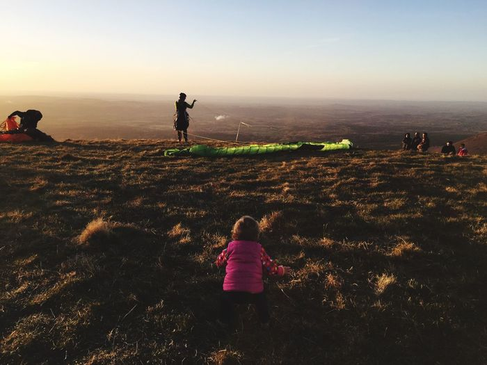 Rear view of baby girl on mountain peak during sunset