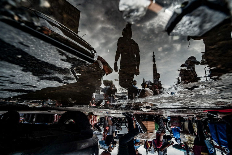 Reflection of people on puddle in city during rainy season