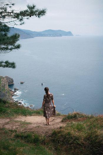Rear view of women on mountain by sea