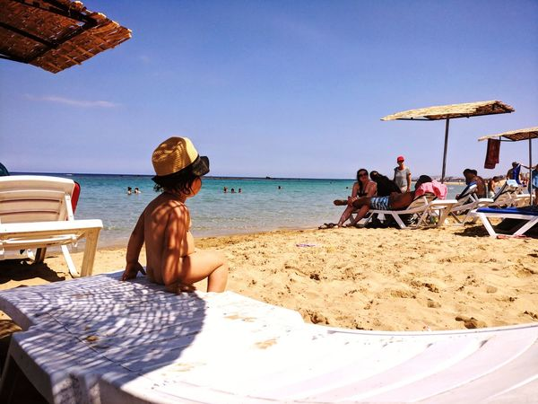 Toddler boy sat on sunbed and looking through the beach Sea Alone Romantic Toddler  Boy Rear View Sunny Light And Shadow Holiday Summer Water Sea Beach Sitting Sand Women Clear Sky Men Relaxation Summer Beach Umbrella Sun Hat Sunshade Beach Holiday Sunbathing