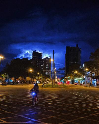 People on illuminated city street against sky at night
