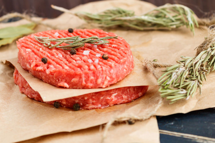 Raw hamburger patties with rosemary