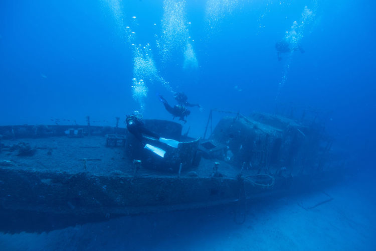 High Angle View Of Scuba Divers Swimming Over Ship Wreck Undersea