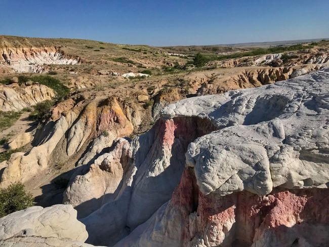 High angle landscape of multi colored rock formations in Colorado Paint Mines Interpretive Park Colorful Rocks Unusual View Colorado Rock Nature Tranquility Sunlight Scenics - Nature Tranquil Scene Solid Sky Beauty In Nature Day Non-urban Scene No People Environment Land Outdoors Clear Sky Rock - Object Landscape Rock Formation Shadow