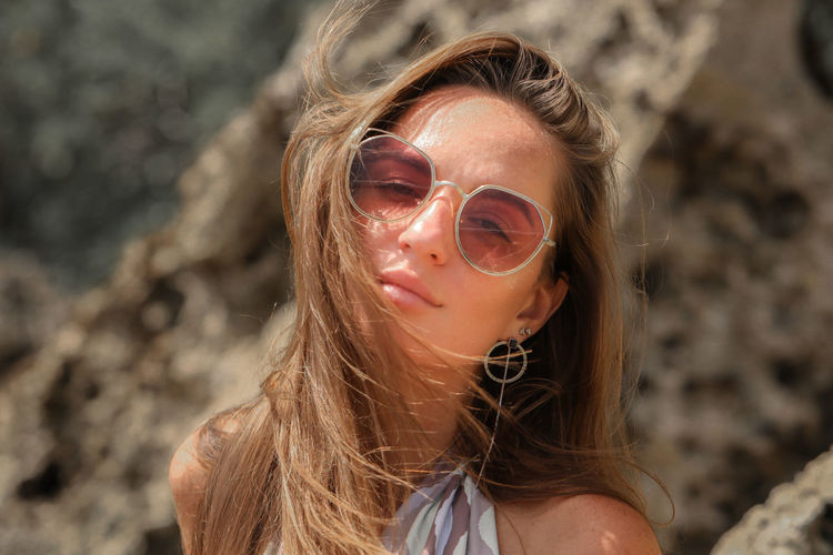 Close-up portrait of a young woman wearing sunglasses