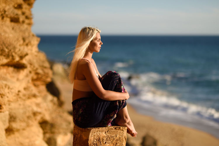 Side view of young woman with eyes closed sitting at beach