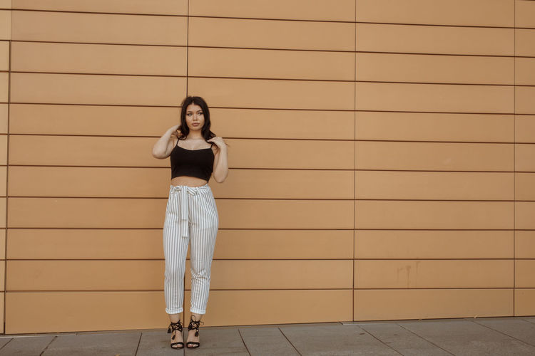 Full Length Of Fashionable Young Woman Standing Against Wall
