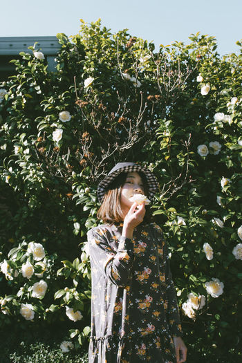 Portrait Of Woman Holding Flower While Standing Against Plants