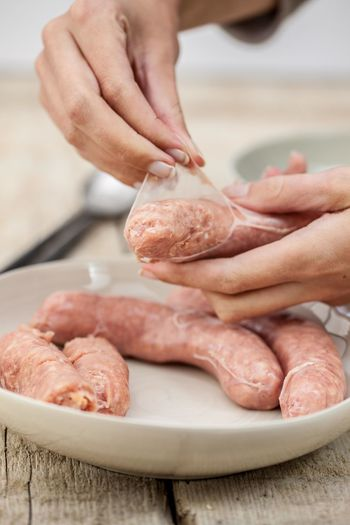 Cropped image of hand holding peeling sausage in bowl