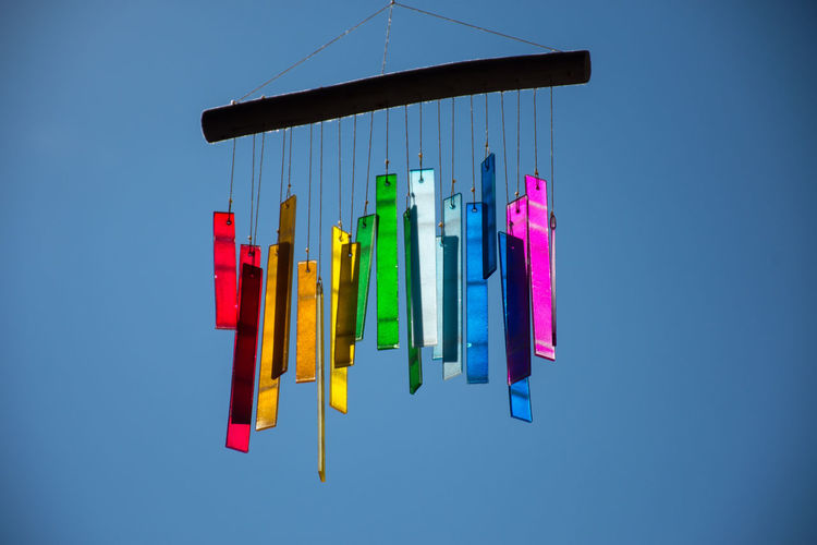 Colorful wind chime hanging against clear blue sky