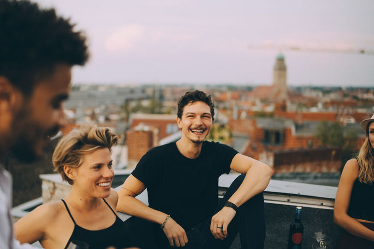 Smiling young man and woman in city against sky