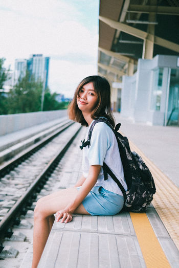 Portrait of smiling woman sitting on railroad track