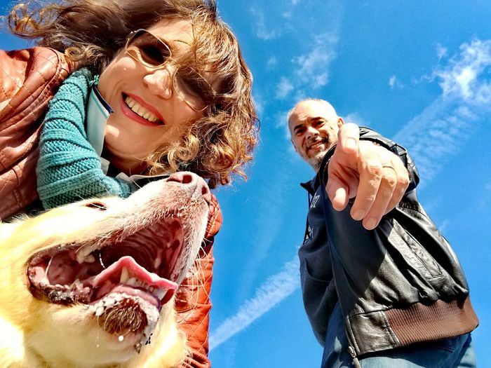 Low angle portrait of man and woman with dog against sky