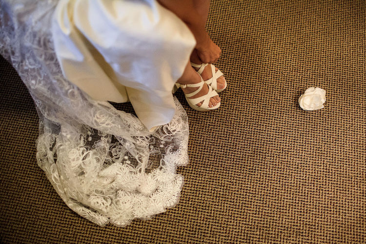 Low Section Of Bride Wearing Sandals While Standing On Carpet