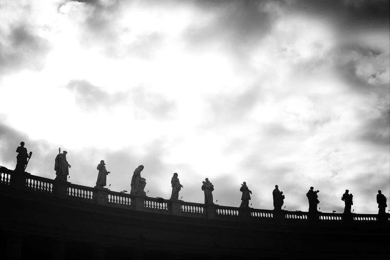 Statues On Railing Against Cloudy Sky