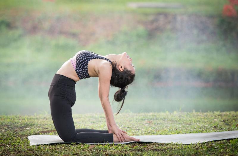 Woman doing yoga on field