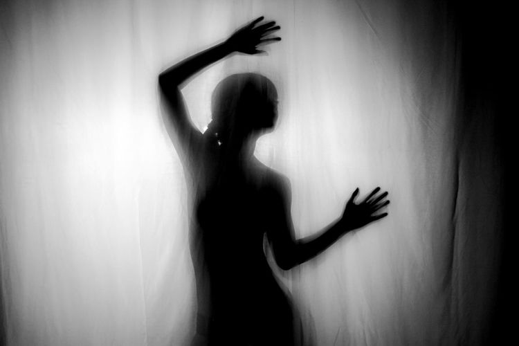 Silhouette woman with arm raised seen through curtain at home