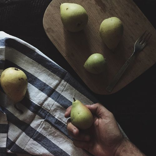 Cropped image of person holding pear at table