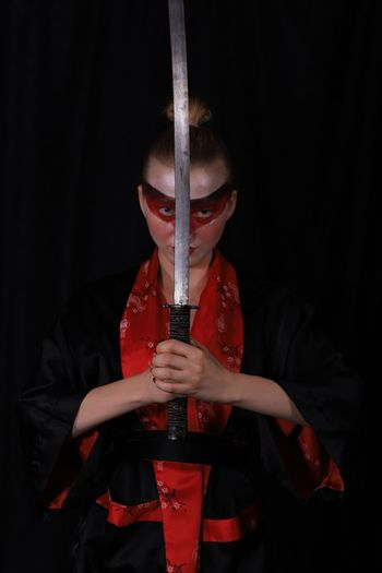 Portrait Of Man In Traditional Clothes Holding Sword Over Black Background