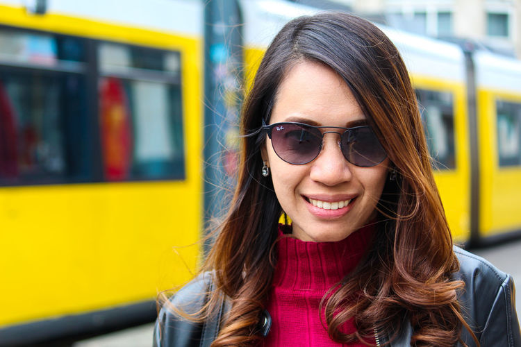 Portrait of a smiling young woman in train