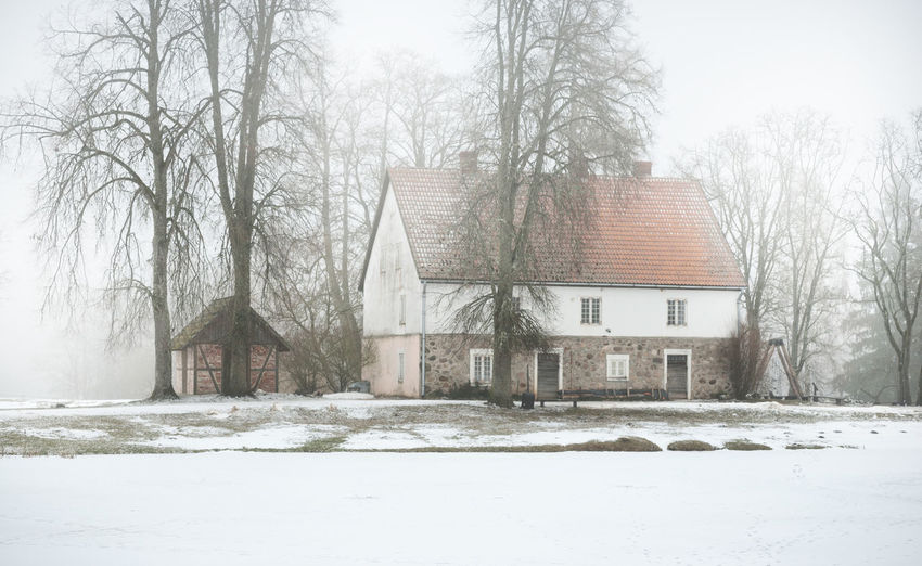 Snow covered houses and trees on field during winter