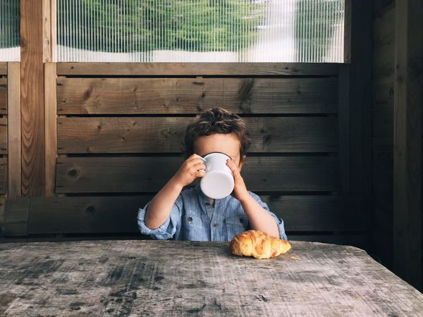 A boy and his croissant. Lifestyles Sitting In Front Of Day Casual Clothing Wooden Table Breakfast Drinking cup Croissant toddler Young Boy boy Morning happy Everyday holiday Camping glamping Camp