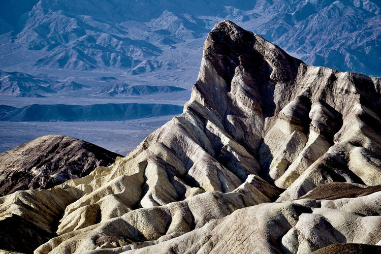 Scenic view of jagged white mountains against distant barren landscape