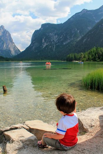 child on the shore of the lake Landscape Child Colorful Hiking Italy Alps Dolomiti Scenic Nature_collection Nature EyeEm Best Shots EyeEmNewHere EyeEm Nature Lover EyeEm Selects EyeEm Gallery Outdoors Mountain Sitting Males  Childhood Lake Boys Summer Rear View Lakeshore Pedal Boat Hiker Calm Looking At View Tranquil Scene
